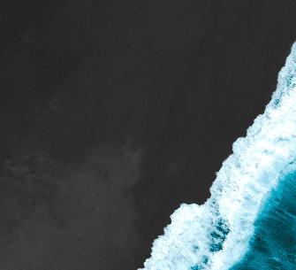 Wave crashing into a dark sandy shore