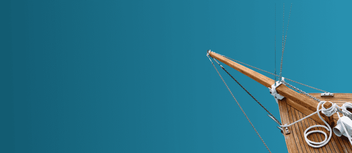 Wooden bow of boat with light blue background