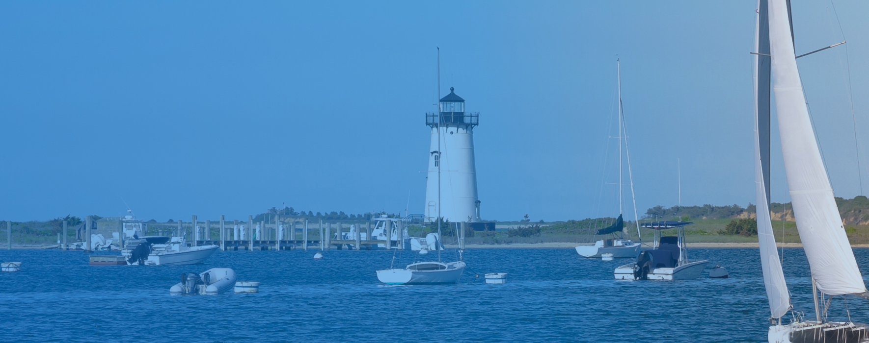 Lighthouse near shore filled with boats