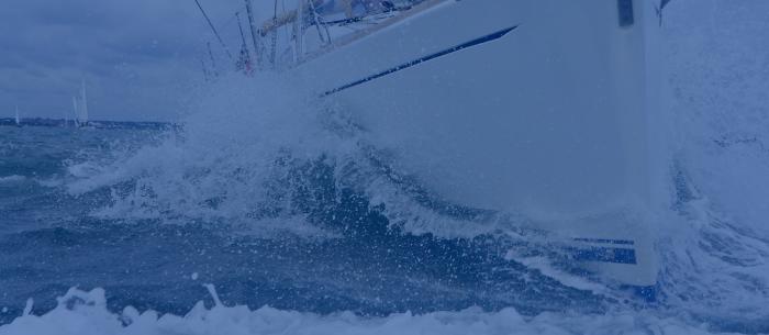 Bow of a white ship crashing into a wave